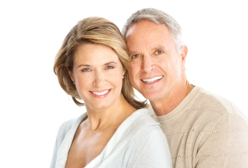 An older couple smiling to show their veneers