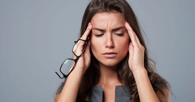 A woman that suffers from frequent headaches messages her temples