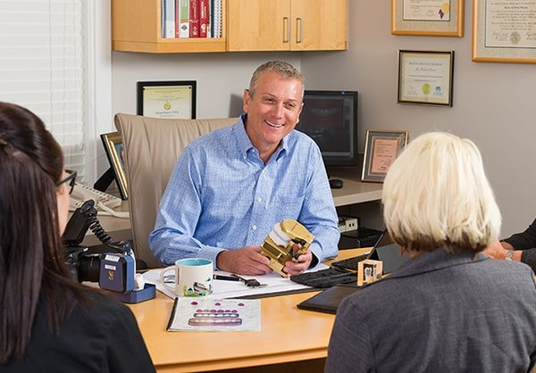 Dr. Richard Dervin, a dentist in Shawnee, KS sitting at his desk talking with patients.
