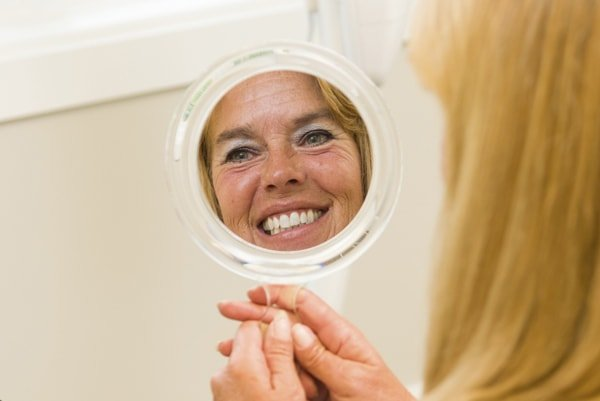 A woman holding a mirror with her smiling reflection showing because her dentist in Shawnee, KS, and has a serene office with many amenities.