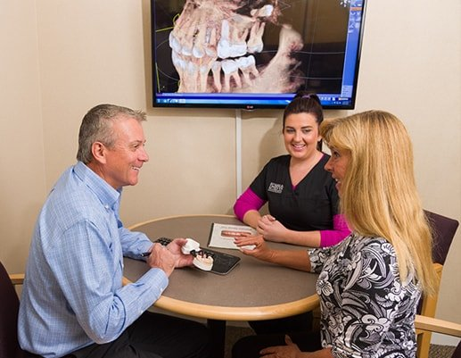 Dr. Dervin, a dentist in Shawnee, KS sitting at a table with a patient and one of his Hygienist discussing treatment options.