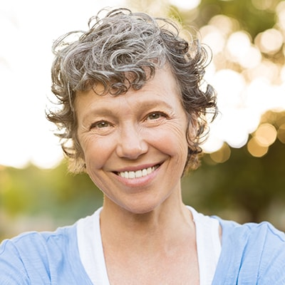 Cosmetic Dentistry Shawnee, KS - An older attractive woman with short curly hair and a light blue shirt smiling because of the high-quality crowns and bridges she received at Richard M. Dervin, DDS.