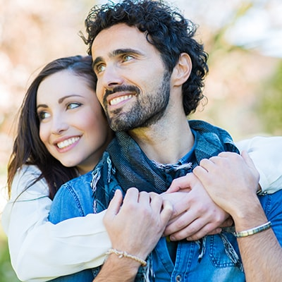 A young couple embracing and smiling because they improved their smiles with porcelain veneers which are offered as part of our Shawnee dental services.