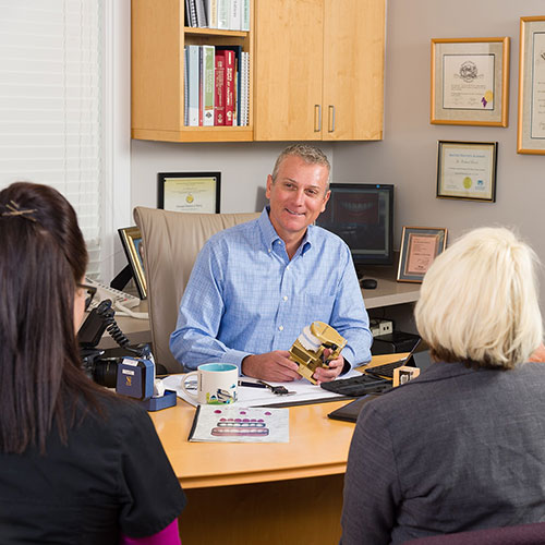 Dr. Richard Dervin sitting in his office talking to his team members.