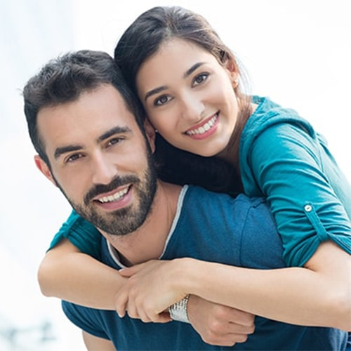 A woman hugging a man with arms around him.